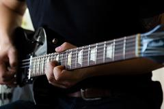 Guitarist play on black electric guitar - stock photo