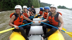 Happy Asian people rowing at full speed on whitewater rafting boat, on board - stock footage