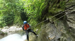 Stock Video Footage of Canyoning guide descending a waterfall rappelling