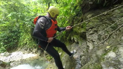 Canyoning guide descending a waterfall rappelling Stock Footage