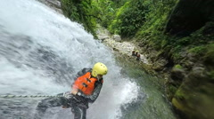 Young adult descending 15m high waterfall in Ecuadorian rain forest, slow motion Stock Footage