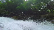 Stock Video Footage of Canyoning instructor rappelling large water volume waterfall, shot from below,