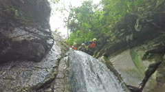 Young adult female jump into river mountain waterfall, canyoning expedition in Stock Footage
