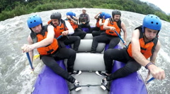 Nine people group whitewater rafting on rainy day, on board mounted action Stock Footage