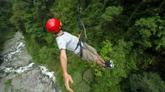 Adult men riding a zip line, cable mounted camera, model released footage Stock Footage