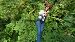 Young women on zip line over the dense rainforest, 3rd person camera - stock footage