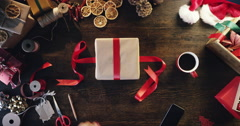 Top view woman wrapping christmas presents at wooden desk hands from above - Red - stock footage