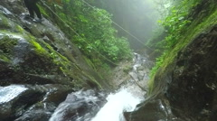 Asiatic tourist women is sent by zip line over the waterfall while canyoning, Stock Footage
