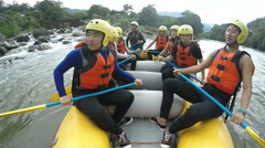 Group of nine Asiatic people whitewater rafting rowing very slowly, on board Stock Footage