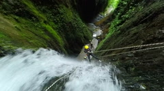 Tourist descent a huge waterfall along with a canyoning instructor, 1080p - stock footage