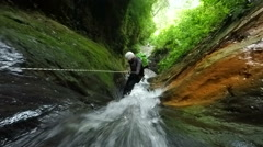 Canyoning instructor rappelling close to impressive waterfall, includes audio, - stock footage