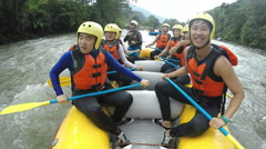 Asian men making funny faces while whitewater rafting trip, slow motion onboard Stock Footage