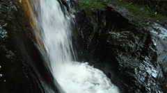 Tourist sliding into waterfall and is pulled back into water stream, with audio, Stock Footage