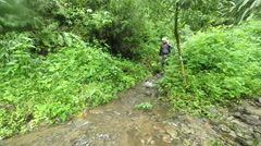 Canyoning instructor in Ecuadorian rain forest passes static camera, slow Stock Footage