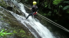 Asiatic girl rappelling a waterfall in Ecuadorian rainforest, static camera, Stock Footage