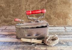 Retro still life with old rusty iron ,paper roll and rope reel on wooden tabl - stock photo