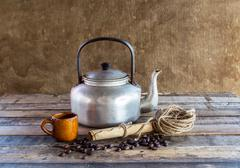 Old kettle,paper roll,rope reel and coffee beans on wooden background Stock Photos