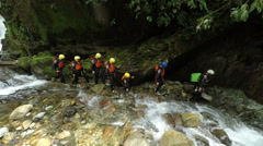 Group of tourist, adults and kids on the Cashaurco canyon near Banos, pan left Stock Footage