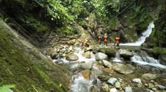 Canyoning zip line in Ecuadorian rainforest, group of tourist descent over Stock Footage