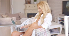 Woman relaxing at home with her laptop computer Stock Footage