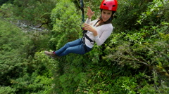 Beautiful young women sliding on zip line, camera rotates around the talent, - stock footage