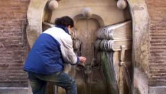 Guy is drinks water from the Fountain of the Books (Fontana dei Libri). Rome Stock Footage