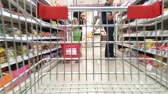 Shopping cart moving through supermarket - stock footage