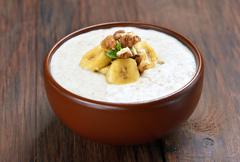 Oatmeal porridge with walnuts and bananas Stock Photos