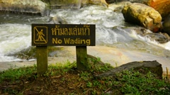 FullHD video - Wooden safety sign cautions tourists not to wade in the rough Stock Footage