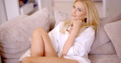 Pretty Blond Woman on Sofa Looking at Camera Stock Footage
