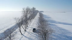 Stock Video Footage of Aerial view of a car driving on the empty snowy road.