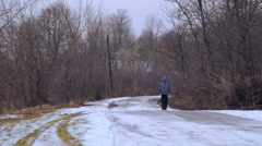 A teenager with a backpack goes on winter road in the village. Stock Footage