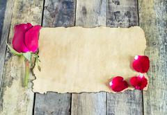 Fresh red rose and old paper on a wooden background. - stock photo