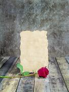 Fresh red rose and old paper on wooden background Stock Photos