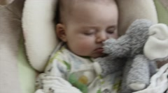Newborn boy sleeping in swing with stuffed animal Stock Footage