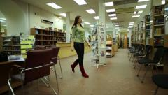 Woman in library choosing books Stock Footage