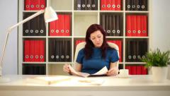 Stock Video Footage of Woman reading a catalog in the office