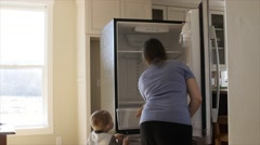 Child helping his mother clean the kitchen fridge - stock footage