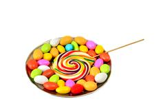 Striped lollipop and multicolored smarties isolated - stock photo