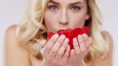 Beautiful woman blowing rose petals Red Epic Dragon Stock Footage