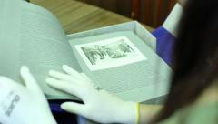 The girl in the library leafing through a rare book, folio Stock Footage