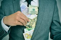 Man in suit putting euro, dollar and pound bills in his jacket, depicting con Stock Photos