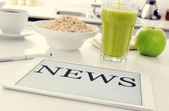 breakfast and news at the kitchen table - stock photo