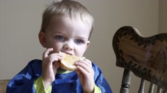 Toddler eats a grilled cheese for lunch Stock Footage