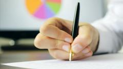 Person writing an evaluation Stock Footage