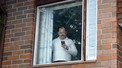 Adult man talking on cellphone by the window Stock Footage