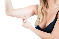 Woman showing flabby arm - stock photo
