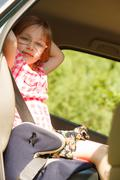 Road and safety. Little girl sitting in car seat. Stock Photos