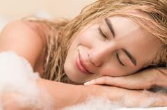 closeup of beautiful blond young woman having a bubble bath - stock photo