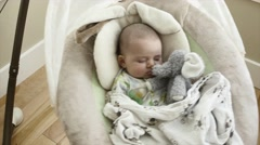 A newborn boy sleeping in swing with stuffed animal Stock Footage